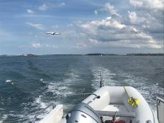 Jets thunder overhead as we cruise beneath the flightpath into Logan.